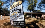 A realty sign is posted in front of a home for sale in this Jan. 8, 2015 file photo. (AP / Rogelio V. Solis)
