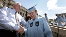 Columbia University janitor Gac Filipaj, center, is congratulated by his boss, Donald Schlosser, the assistant vice president of facility operations, during the Columbia University School of General Studies graduation, Sunday, May 13, 2012, in New York. (AP Photo/Jason DeCrow)