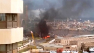 In this image made from video posted by a Libyan blogger, the Cortinthia Hotel is seen under attack in Tripoli, Libya, Tuesday, Jan. 27, 2015. (@AliTweel via AP video)