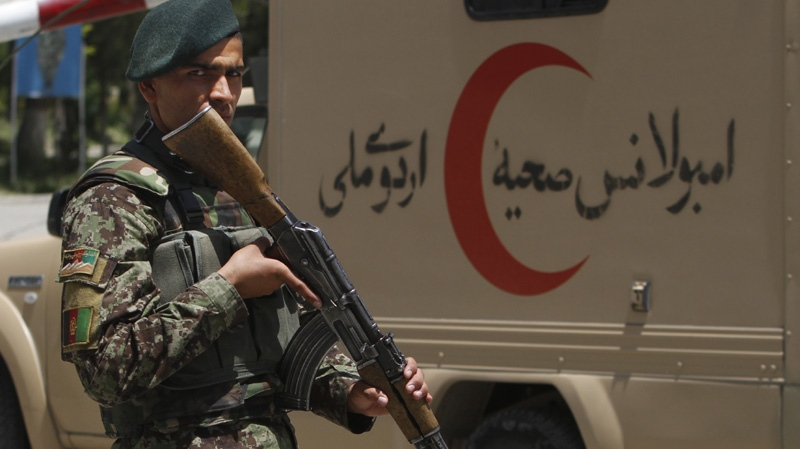 An Afghan National Army soldier patrols the gate of the military hospital next to an ambulance in Kabul, Afghanistan, Sunday, May 13, 2012. 2012.
