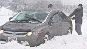 Two men help out an car that is stuck in the snow on University Street during a snow storm in Moncton on Tuesday, Jan. 27, 2015. (Marc Grandmaison / THE CANADIAN PRESS)