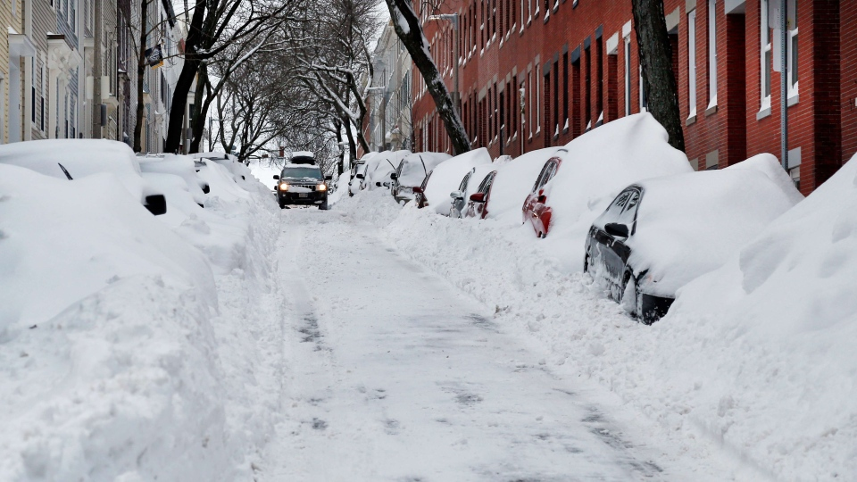 A car makes its way down a street filled with snowed-in vehicles in Boston's Charlestown section, Wednesday, Jan. 28, 2015. (AP / Elise Amendola)