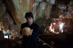 Dr. Omry Barzilai of Israel's Antiquities Authority holds an ancient skull found inside a cave near the Israeli northern city of Nahariya. Wednesday, Jan. 28, 2015. (AP / Dan Balilty)
