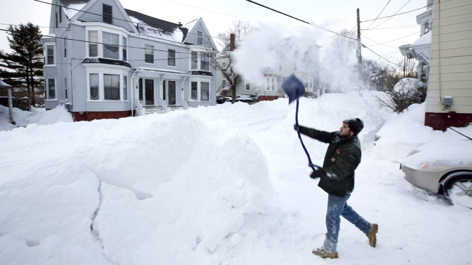 Tyler Whitney throws a load of snow on top of a growing snowbank in front of his home while shoveling out after a winter storm, in Portland, Maine, Wednesday, Jan. 27, 2015. (AP / Robert F. Bukaty)