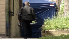 A tent is seen as police investigate after the body of 19-year-old John James was found in Kitchener, Ont. over the weekend, Monday, May 14, 2012.