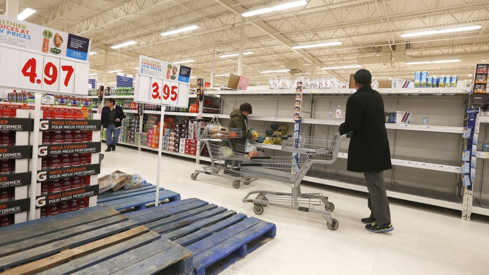 Late night shoppers are greeted with empty shelves and pallets after authorities issued a boil water advisory after a positive E.coli test, in Winnipeg, Tuesday, Jan. 27, 2015. (John Woods / THE CANADIAN PRESS)