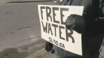 A sign is held in Winnipeg on Jan. 29, 2015. Shoal Lake 40 First Nation, which provides Winnipeg with water through an aqueduct, has been under a boil-water advisory for 17 years.