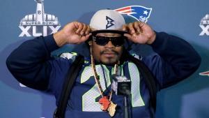 Marshawn Lynch of the Seattle Seahawks adjusts his cap during an interview ahead of NFL Super Bowl XLIX football game in Phoenix, Ariz., on Thursday, Jan. 29, 2015. (AP Photo/Matt York)