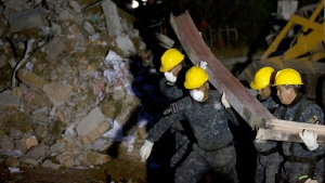 Rescue workers haul a bent beam from the rubble as the search for survivors continues into the night amongst the rubble of a maternity and children's hospital after a gas truck exploded in Cuajimalpa on the outskirts of Mexico City, Thursday, Jan. 29, 2015. (AP / Rebecca Blackwell)