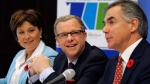 Alberta Premier Jim Prentice (right) speaks as B.C. Premier Christy Clark (left) and Saskatchewan Premier Brad Wall (centre) look on in Regina, Nov. 6, 2014. (THE CANADIAN PRESS / Michael Bell)