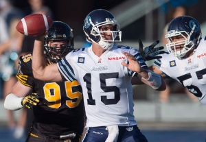 Toronto Argonauts quarterback Ricky Ray, centre, makes a pass while under pressure from Hamilton Tiger-Cats' Brian Bulcke, left, and Argos teammate Tyler Holmes during first quarter CFL pre-season action at University of Toronto's Varsity Stadium in Toronto, Ont. on Thursday, June 19, 2013. (Darren Calabrese/THE CANADIAN PRESS)