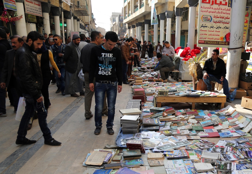 In this Friday, Jan. 23, 2015 photo, Iraqis look at books on al-Mutanabi Street, home to the city's book market in central Baghdad. (AP Photo/Karim Kadim)