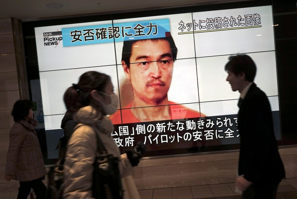 People walk by a screen showing TV news reports of Japanese hostage Kenji Goto, held by the Islamic State group, in Tokyo Saturday, Jan. 31, 2015.  (AP/Eugene Hoshiko)