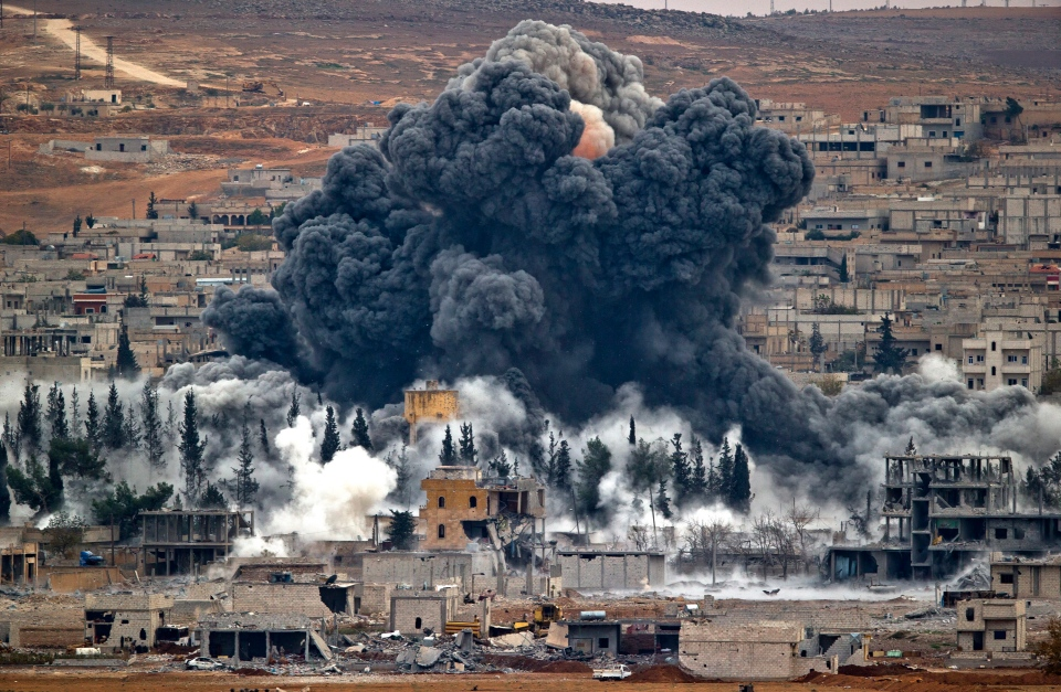 Smoke rises from the Syrian city of Kobani, following an airstrike by the U.S.-led coalition, seen from a hilltop outside Suruc, on the Turkey-Syria border, Monday, Nov. 17, 2014. (AP / Vadim Ghirda)
