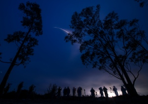In this photo taken with a long exposure, and provided by NASA, spectators watch as a Delta 2 rocket carrying the SMAP satellite launches on Saturday, Jan. 31, 2015 from Vandenberg Air Force Base, Calif. (Provided / NASA / Bill Ingalls)