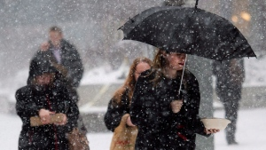 A women uses an umbrella to take cover from the blizzard like conditions in Toronto on Wednesday, March 12, 2014. (Nathan Denette / The Canadian Press)