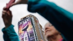 A banner of the Vince Lombardi Super Bowl Trophy decorates a building as fans take photos of the downtown festivities, Saturday, Jan. 31, 2015, in Phoenix. (AP / David Goldman)