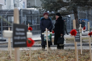 Crosses placed by activists and bearing the names of 30 people who died in shelling in Mariupol on Jan. 24 are seen in the foreground, as women talk near the Russian Embassy in Kyiv, Ukraine on Sunday, Feb. 1, 2015. (AP / Sergei Chuzavkov)