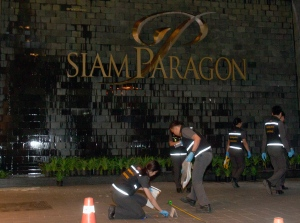 Thai police forensic officers investigate near the front of the Siam Paragon shopping mall, the site of a blast in Bangkok, Thailand on Sunday, Feb. 1, 2015. (AP / Sakchai Lalit)