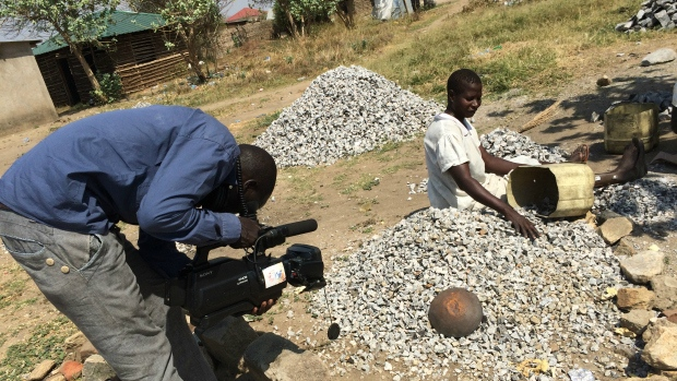 Cameraman Hatim shoots video of a woman breaking stones.