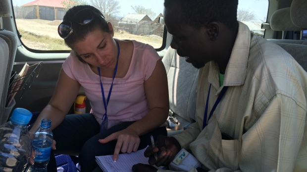 Kayla and Taban in the field working on the script he will deliver on camera.