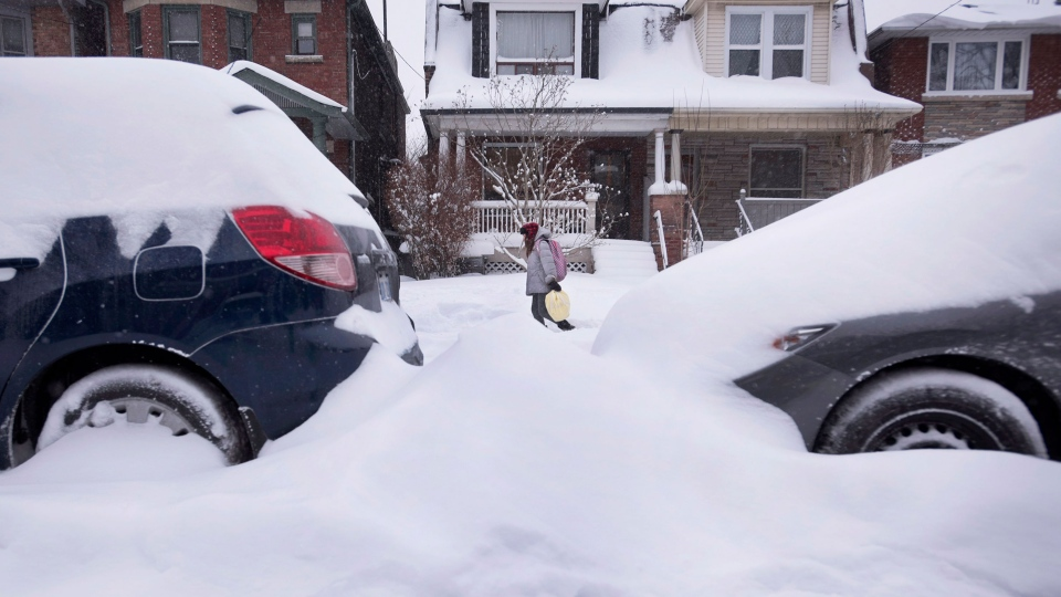 A girl walks past cars buried in snow after a winter storm hit Toronto with strong winds and heavy snow on Monday, Feb. 2, 2015. (Darren Calabrese /THE CANADIAN PRESS)