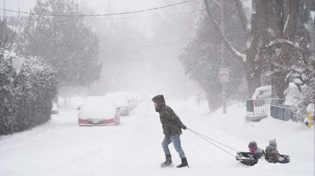 A woman pulls children in a sled down Sorauren Avenue in Toronto as a storm hits with strong winds and heavy snow on Monday, February 2, 2015. (Darren Calabrese/ THE CANADIAN PRESS)