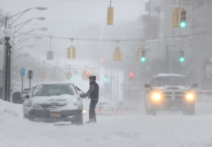 A motorist parked on Genesee Street clears window during Monday's snowstorm in Utica, N.Y. Feb. 2, 2015. (Observer-Dispatch, Mark DiOrio)