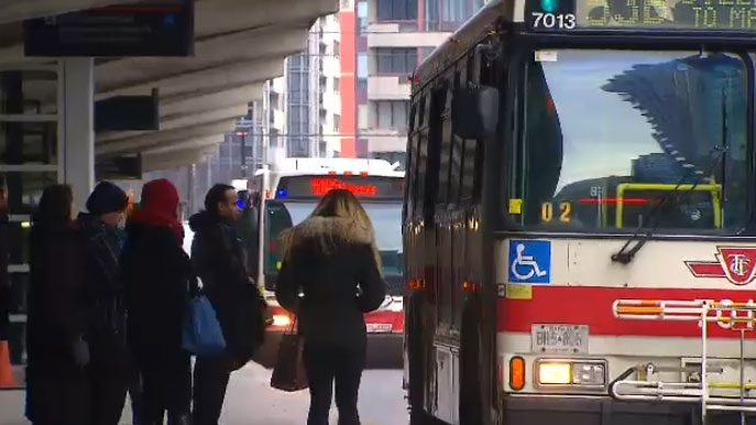 Transit users wait to board a TTC bus in Toronto on Monday, Feb. 2, 2015.