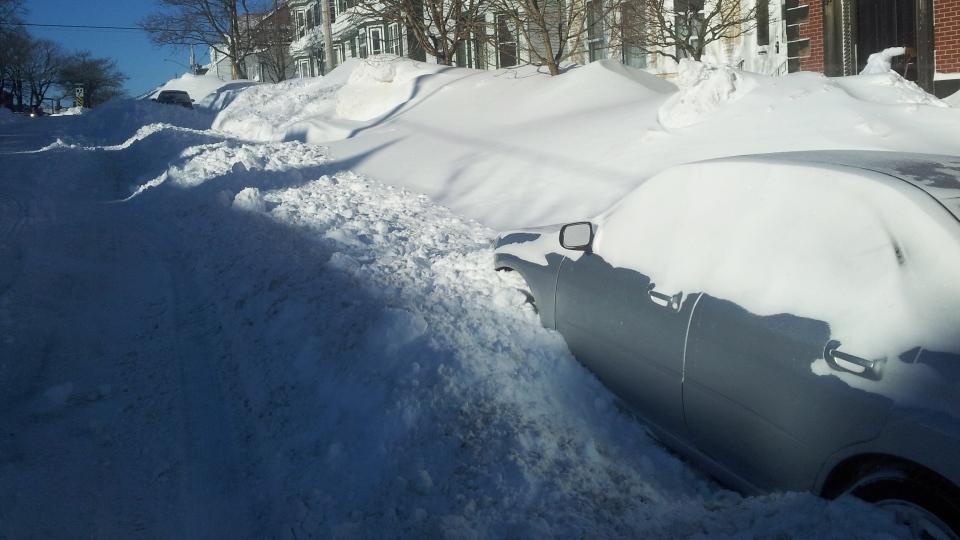 A car covered in snow, sits on a street in Saint John, N.B., Tuesday, Feb. 3, 2015. (Darrell Johnston / CTV News)