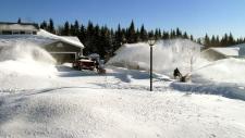 Blowing snow off roads in Saint John, N.B.