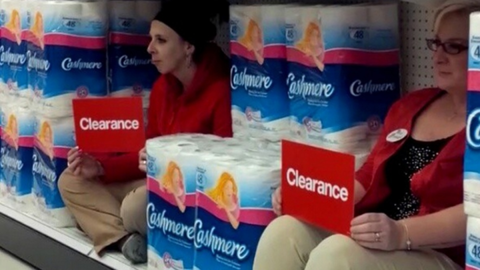 Two employees at an Ottawa-area Target sit on a shelf while holding clearance signs in this image from video posted Jan. 22, 2015. (Instagram / Nat MacDonald)