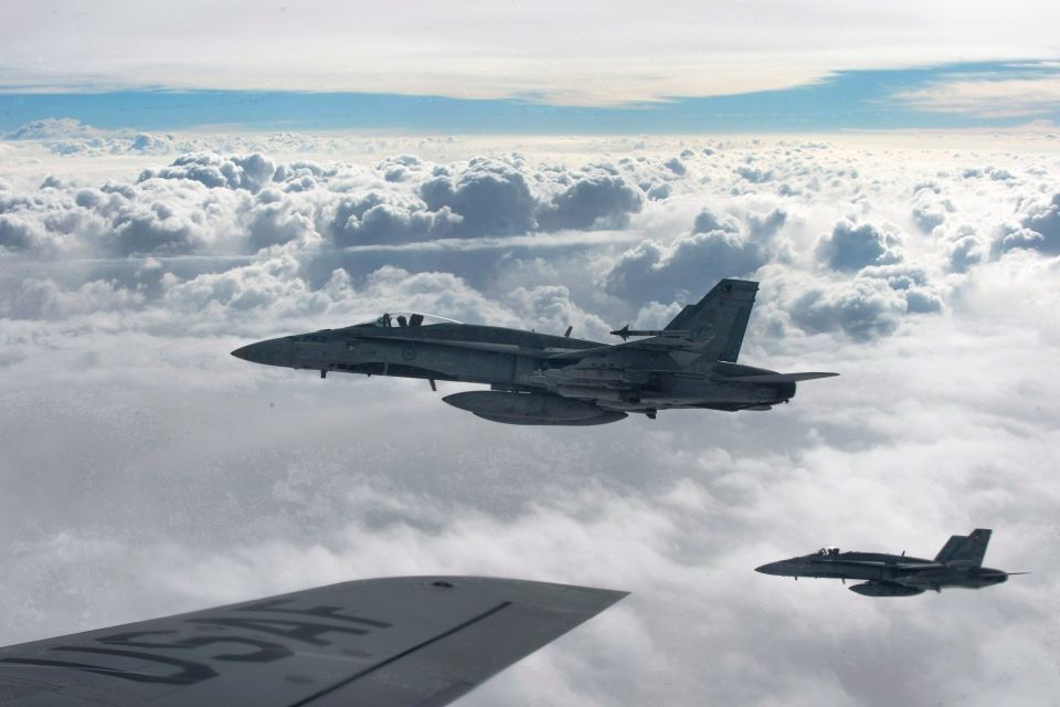 Royal Canadian Air Force CF-18 Hornets depart after refueling with a KC-135 Stratotanker assigned to the 340th Expeditionary Air Refueling Squadron on Oct. 30, 2014, over Iraq. (Submitted photo U.S. Air Force / Staff Sgt. Perry Aston / The Canadian Press)