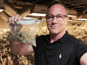 Kevin Newman holds up a bag of marijuana inside a legal dispensary in Denver, Colo.