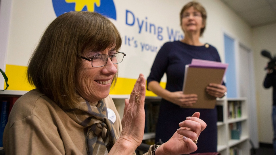 Linda Jarrett, left, applauds Wanda Morris, CEO of Dying with Dignity, as she speaks to the media group's offices in Toronto after a Supreme Court decision on doctor-assisted death, on Friday, Feb. 6, 2015. (Chris Young / THE CANADIAN PRESS)
