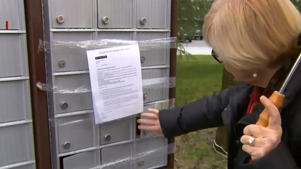 Julie Parker inspects a taped-up community mailbox after it was looted by thieves in Surrey, B.C. on Saturday, Feb. 7, 2015.