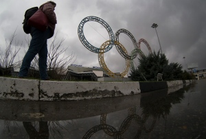 A woman walks past Olympic rings near the Sochi airport at the Black Sea resort of Sochi, Russia, Friday, Jan. 9, 2015. (AP / Dmitry Lovetsky)