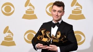 "Sam Smith poses in the press room with the awards for best new artist, best pop vocal album for ""In the Lonely Hour"", song of the year for ""Stay With Me"", and record of the year for ""Stay With Me"" at the 57th annual Grammy Awards at the Staples Center in Los Angeles on Sunday, Feb. 8, 2015. (Chris Pizzello/Invision/AP)"