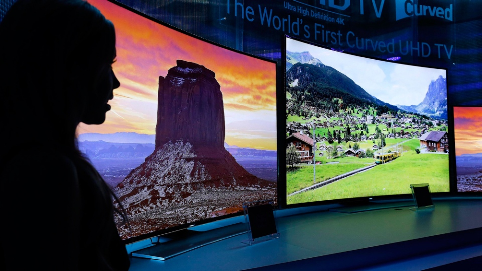 A model stands next to a Samsung display at the International Consumer Electronics Show in Las Vegas last year.  Samsung reminds users to watch what they say in front of the TV, because their device could be picking up their personal information as well. (AP / Julie Jacobson)