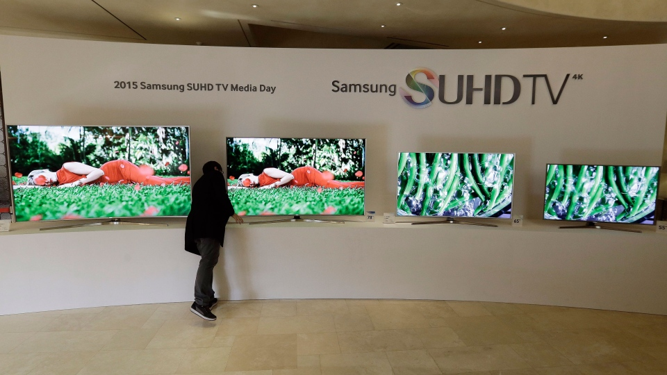An employee of Samsung Electronics Co. checks its SUHD 4K TVs on display outside the venue of a press conference in Seoul, South Korea, Thursday, Feb. 5, 2015. (Ahn Young-joon)