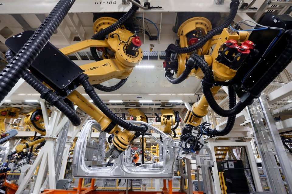 Robots install rivets on a 2015 Ford F-150 truck at the Dearborn Truck Plant in Dearborn, Mich. on Nov. 11, 2014.  (AP / Paul Sancya)