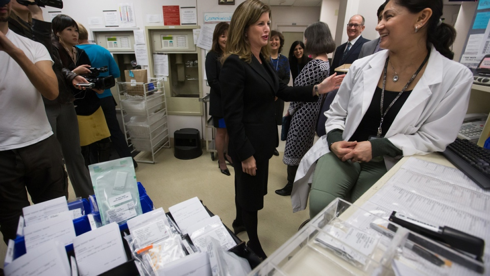 Federal Health Minister Rona Ambrose, centre, talks with Vancouver General Hospital pharmacy technician supervisor Kaldip Mattu after announcing new regulations aimed at pharmaceutical companies during a news conference in Vancouver, on Tuesday, Feb. 10, 2015. (Darryl Dyck / THE CANADIAN PRESS)