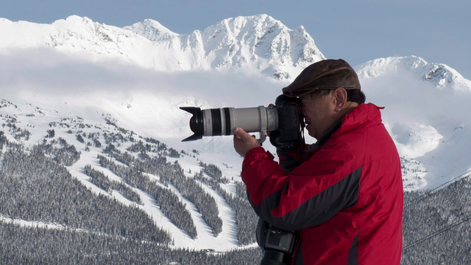 Blackcomb mountain is pictured in the background as a photographer takes a picture on top of Whistler mountain in Whistler, B.C., Friday, Dec. 26, 2014. (Jonathan Hayward / THE CANADIAN PRESS)