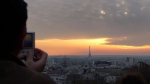A man watches the sun set over the city skyline with Eiffel Tower seen at right in Paris, France, Sunday, March 20, 2011. (AP / Peter Dejong)