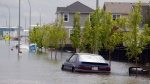 Cars sit parked in flood water in a restricted neighborhood in High River, Alta. on July 4, 2013. A RCMP watchdog says Mounties improperly took guns from flooded homes in High River. (Jeff McIntosh / THE CANADIAN PRESS)