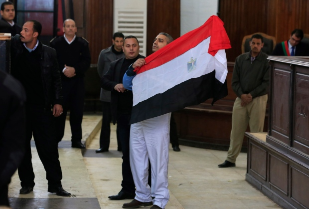 Canadian Al-Jazeera English journalist Mohamed Fahmy holds up an Egyptian flag after a retrial a courthouse near Tora prison in Cairo, Egypt, Thursday, Feb. 12, 2015. (AP / Hassan Ammar)