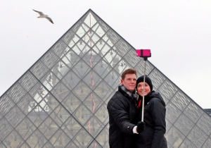 Two tourists use a selfie stick in front of the Louvre Pyramide in Paris, Tuesday, Jan. 6, 2015. (AP / Remy de la Mauviniere)