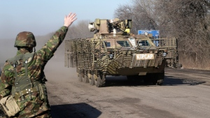A Ukrainian government troop waves to a armored vehicle driving on the road towards Debaltseve near the town of Artemivsk, Ukraine, Friday, Feb. 13, 2015. (AP / Petr David Josek)