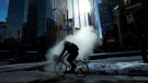 Stream rises from the street as a cyclist makes their way around in the below normal cold weather in Toronto on Friday, February 13, 2015. (Nathan Denette / THE CANADIAN PRESS)