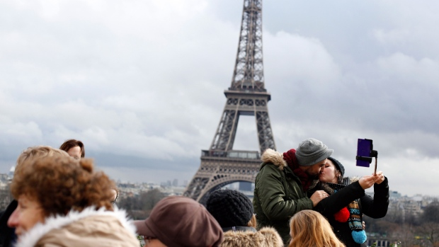 A couple shares a kiss in front of the Eiffel Tower, during Valentine's day in Paris, Saturday, Feb. 14, 2015. (AP T hibault Camus)